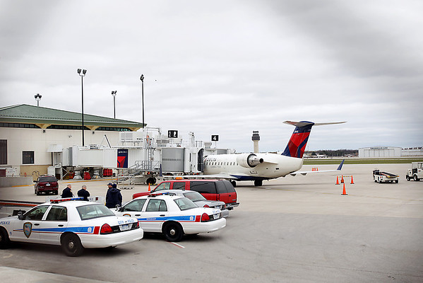 Record-Eagle/Keith King<br /> Police officers stand near Delta Airlines flight 4290, which had to make an emergency landing at Cherry Capital Airport Tuesday, April 17, 2012 after the battery on a portable medical oxygen tank caught fire.