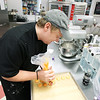 Record-Eagle/Keith King<br /> Len Mayhew, owner of Simply Cupcakes, pipes dough for what will become French macaron cookies.
