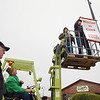 "Record-Eagle/Keith King<br /> Frank Novak, left, of Solon Township, stands near as Larry Bruckner, of Kasson Township, operates a forklift while Adolph Novak, of Solon Township, and Ed Galla, of Cleveland Township, hang a ""Welcome to Cedar"" banner in Cedar on Tuesday after the banner, along with others the group hung, were stored for the winter. The four, who were volunteers for the hanging of the banners, also work with the Cedar Polka Festival, scheduled for July 5-8."