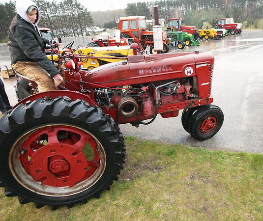 Record-Eagle/Keith King<br /> Hannah Thon turns off her Farmall Super M tractor on a rainy Friday, during Tractor Day at Kingsley High School. Students are able to drive tractors to school that day.
