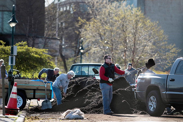 Record-Eagle/Jan-Michael Stump<br /> People shovel some of the 120 yards of free compost donated by Traverse City at the Sarah Hardy Farmer's Market on Saturday, which also featured a white pine seedling giveaway and recycling dumpster, in celebration of Earth Day.