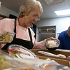 Record-Eagle/Douglas Tesner<br /> Cherly Nelson, kitchen supervisor at the Goodwill Inn, looks over food delivered by Bob Cullen from Food Rescue of Northwest Michigan.