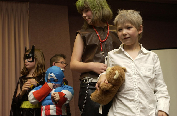 Record-Eagle/Garret Leiva<br /> Caden Loose, 5, of Elk Rapids, center, shows off his Captain America moves during a costume contest Saturday evening at the Cherry Capital Con 09 held at the Grand Traverse Resort & Spa. Also competing in the kids category were Milah Loose, 9, as Bat Girl, Abran Loose, 10, as Living Lighting, Harley Butler, 7, as Near, and Sonja Butler, 10, as Mello. The costume contest, which included adult divisions, was part of a two-day convention that featured panels with comic book artists and writers, vendors and opportunities to show portfolios to publishers.