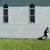 Record-Eagle photo/Jan-Michael Stump<br /> Kathy Fitch mows the lawn outside Fitch's School of Dance, which she owns, in Kalkaska on Thursday afternoon. The school has been in the building -- a former church -- for 17 of its 32 years in business.