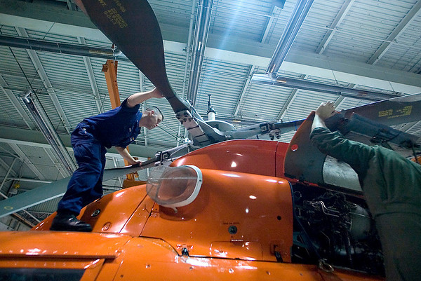 Record-Eagle photo/Jan-Michael Stump<br /> Coast Guard AET1 Dave Hinds, left, and AMT2 Ted Mace, do a post-flight inspection on one of Air Station Traverse City's five HH-65C helicopters on Friday afternoon. Traverse City is applying to be designated the tenth U.S. Coast Guard City in the country.