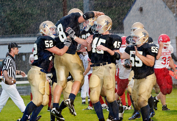 Record-Eagle/Douglas Tesner<br /> Traverse City St. Francis players celebrate after Joe Kerridge (8) scores a touchdown Friday night against Benzie Central at Thirlby Field in the season-opening game for both teams.