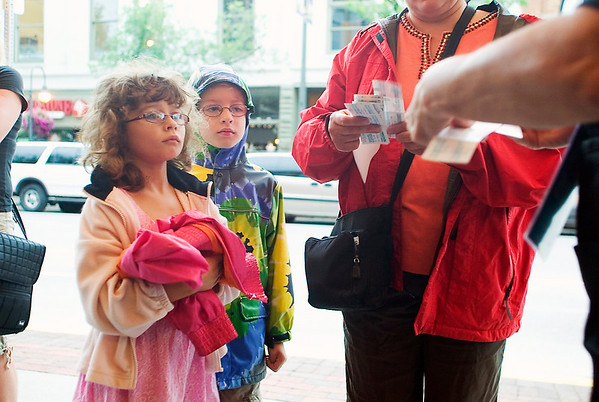 "Record-Eagle/Jan-Michael Stump<br /> Twin siblings, from left, Margaret, and Peter Worden, 7, of Traverse City and their mother, Michele, have their tickets collected at the State Theatre for Wednesday morning's ""The Secret of Kells."""