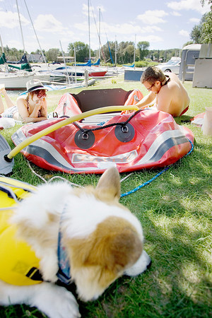 Record-Eagle/Keith King<br /> Justin Rowe, right, of Suttons Bay, applies patches to a boat he recently purchased while Haley Silverman, of Chicago, relaxes in the sun, as their dog, Tails, lies near in Suttons Bay.
