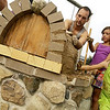 Record-Eagle/Garret Leiva<br /> Mia Kuschell, Lauren Kuschell, center, and Mike Powers, of SEEDS, use their hands to spread clay as they help construct a stone pizza oven Saturday in the Grand Traverse Area Children's Garden. Volunteers used a clay mixture to build up a dome on the pizza oven behind the Traverse Area District Library. The oven will feature a 27 inch inside diameter area to bake pizzas topped with ingredients grown in a kitchen garden. Volunteers started building the pizza oven base in July. The oven will be used in the Children's Garden Roots to Mouth program.