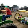 "Record-Eagle/Keith King<br /> Darwin Parsons, left, of Montague, sits in his 1941 John Deere H tractor while Al Conklin, far right, of Hastings, sits in his motorized grain drill along with Leslie Critzer, of Galien, as they wait in line as part of a parade Friday during the 43rd annual Buckley Old Engine Show. ""I asked him if I could ride along on here and he said I could; I'm so excited,"" Critzer said."