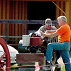 Record-Eagle/Jan-Michael Stump<br /> Dave McCall, left, and Bob Voice talk next to Voice's International Harvester Famous engine Tuesday at the The Buckley Old Engine Show, which runs through Aug 22.