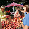 Record-Eagle/Douglas Tesner<br /> Denise O'leary is handed a bag of peach by Arica Whipple at the Sara Hardy Farmers Market in Traverse City. The market is one of many in the area offering fresh fruits and vegetables, baked goods, cider and more.
