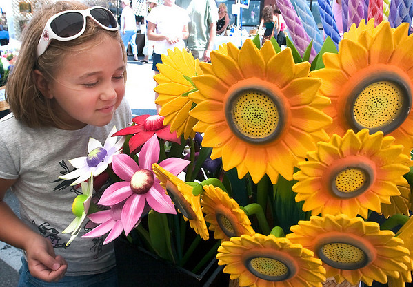 Record-Eagle/Douglas Tesner<br /> Amaya Hall, 7, smells the flowers — the wooden flowers, that is — on Cass Street during Saturday's annual Downtown Art Fair in Traverse City. The juried show attracted 70 exhibitors, most from Michigan but some from as far away as Florida and Arizona, along with hundreds of visitors. The flowers are made from basswood and were displayed by D&M Wooden Flowers.