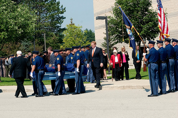 Record-Eagle/Douglas Tesner<br /> Michigan State Police troopers and other officers watch as the body of Sgt. Melvin P. Holbrook is taken from the  Benzie Central High School auditorium after a funeral service. The casket was followed by family members.
