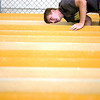 Record-Eagle photo/Jan-Michael Stump<br /> Traverse City Central guard Joel Icard scrapes gum from the bottom of the bleachers at Thirlby Field. Football players from Traverse City Central, Traverse City St. Francis and Traverse City West worked to get Thirlby Field ready for the upcoming season.