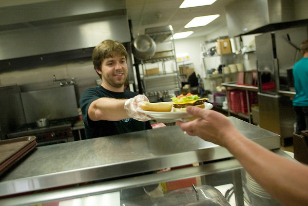 Record-Eagle photo/Jan-Michael Stump<br /> Volunteer Jared Kohler serves dinner to a Goodwill Inn guest on Monday. The food pantry at the Goodwill Inn is at critically low levels after an increase in requests for assistance.