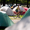 Record-Eagle photo/Jan-Michael Stump<br /> Donna Bour, of Pittsburgh, rides through a sea of tents at the Grand Traverse Civic Center as riders in the Michigan Shoreline Bike Ride, organized by the League of Michigan Bicyclists, camp on the center's grounds during their seven-day, 350-mile tour of Michigan's west shore between Montague and Mackinaw City. The ride was started in 1986 and has more than 400 riders this year.