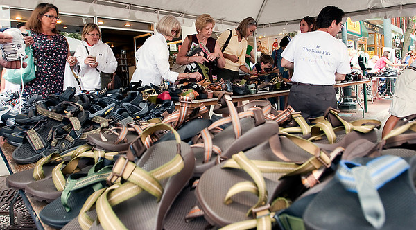 Record-Eagle/Douglas Tesner<br /> Shoppers look for a deal at the Golden Shoes display outside the store during the annual downtown Street Sale.