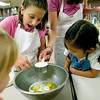 Record-Eagle photo/Jan-Michael Stump<br /> Lauren Kracko, 7, left, and Kelsi Elliott, 6, get help making French toast casserole from instructor Sarah Wilcoxen in a class from NMC's College for Kids program.
