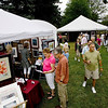 Record-Eagle/Keith King<br /> Festival goers peruse a variety of art Saturday during the Traverse City Wine & Art Festival at the Village at Grand Traverse Commons.