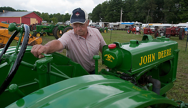 Record-Eagle/Douglas Tesner<br /> Harold Hulst, of Holland, tunes up his 1937 John Deere tractor as he gets it ready for the 43rd Annual Buckley Old Engine Show. The show kicks off this weekend.