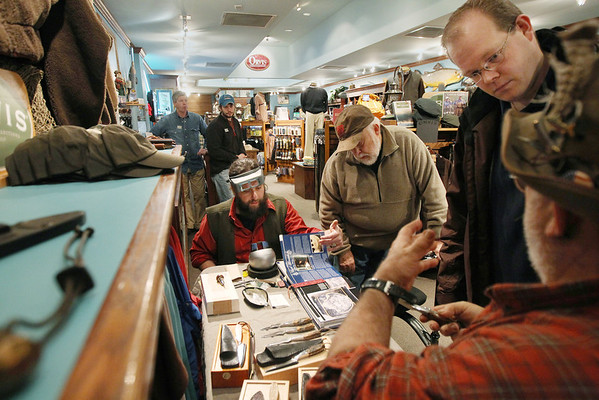 Record-Eagle/Keith King<br /> Andrew Cook, top right, of Bear Lake, listens as Doun Rose II, far right, of Fife Lake, explains his handmade cutlery while David Riccardo, left, of Buckley, shows examples of his engravings to Tom Taylor, of Maple City, at Orvis Streamside Thursday during Men's Night in downtown Traverse City.