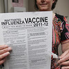 Record-Eagle/Keith King<br /> An employee holds a vaccine information sheet from the Centers for Disease Control and Prevention and the flu vaccine.