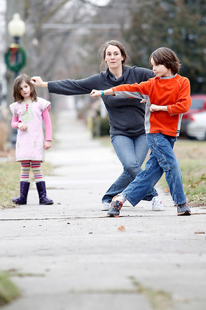 Record-Eagle/Jan-Michael Stump<br /> Miles Riddle, 9, gives his mother, Julia, a kung-fu lesson while sister Maya, 6, watches outside their State Street home on Tuesday afternoon. Miles has been taking lessons for two years.