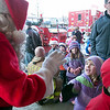 Record-Eagle/Douglas Tesner<br /> Emily Roth and Luke Biggar, both kindergartners at Holy Angels Elementary, are greeted by Santa Claus and firefighters in front of the State Theatre as they donate Christmas presents to the Traverse City Fire Department. In return, the students were rewarded with Christmas movies. Students from both Holy Angels and Immaculate Conception took part in the traditional event.