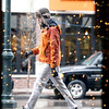 Record-Eagle/Jan-Michael Stump<br /> Walker Thompson, seen through windows reflecting lights, walks down Front Street to do some Christmas shopping in downtown Traverse City.