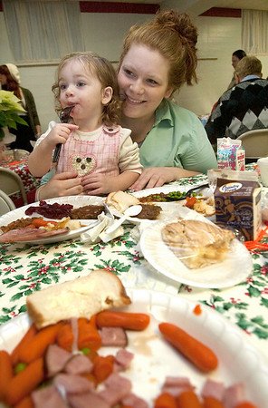 Record-Eagle/Douglas Tesner<br /> Whittney Ager and her daughter Eve, 2, take part in the Community Christmas Dinner at Trinity Lutheran Church in Traverse City.