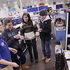 Record-Eagle/Keith King<br /> Kayleigh Marlin, left, a sales associate at Best Buy in Traverse City, assists Lila Dreves, second from left, 17, and her sister Lena Dreves, far right, 17. They were both looking at the Apple iPod Touch, which are to be Christmas gifts from their mother, Freda Dreves, second from right.