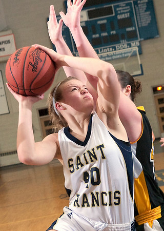 Record-Eagle/Douglas Tesner<br /> St. Francis Liza Erickson goes to the bucket against Glen Lakes Dani Frost in the Lakers 60-54 victory over the Gladiators in the title game of the Katie Heintz Christmas Tournament Tuesday at Traverse City St. Francis.