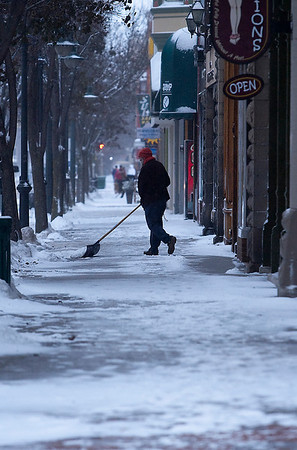 Record-Eagle/Douglas Tesner<br /> Facing blowing winds and bands of lake-effect snow, shopkeepers struggle to keep up with accumulation on the sidewalks on Front Street in downtown Traverse City Monday.