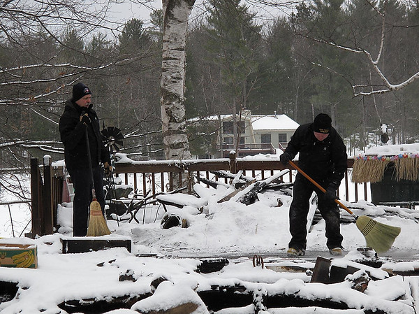 Record-Eagle/Alex Piazza<br /> Fire investigators dust away snow with brooms at the scene of a deadly Christmas morning fire in East Bay Township. The fire's cause remains under investigation.