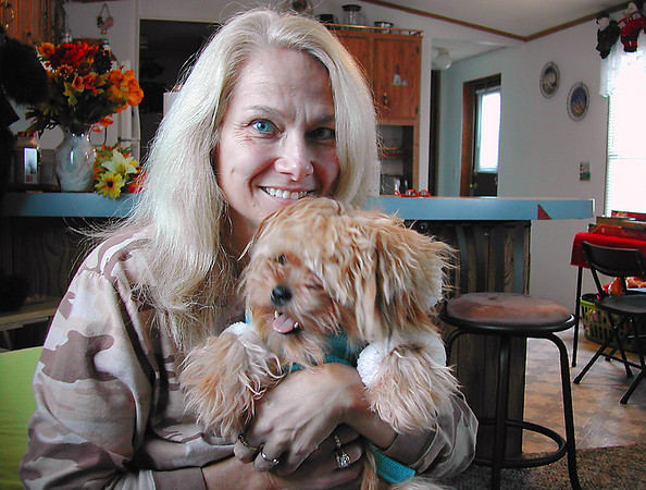 "Record-Eagle/Art Bukowski<br /> Jan Zimmerman cuddles with her dog ""Crikit"" in her Garfield Township home."