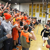 Record-Eagle/Keith King<br /> The Traverse City Central High School student section cheers as the varsity basketball team takes the floor prior to the game against Bay City Western on Tuesday at Traverse City Central High School. The Trojans lost their first game of the season, 65-45.