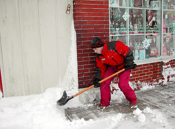Record-Eagle/Sheri McWhirter<br /> Andrew Fritzsche shovels snow from a sidewalk in downtown Kalkaska, where residents awoke on Wednesday to face between six and nine inches of heavy, wet snow.