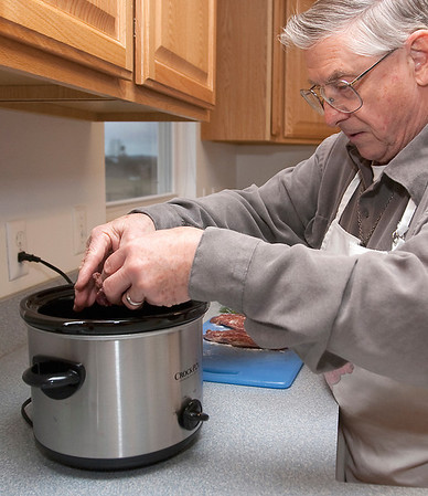 Record-Eagle/Douglas Tesner<br /> Eugene Baughan uses his crockpot (slow cooker) to cook Saucy Venison Steak with Rice.