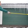 "Record-Eagle/Jan-Michael Stump<br /> Mike DeVries knocks icicles off the roof of his Ninth Street home while putting up storm windows on Monday afternoon. ""We were so busy this fall and the snow caught up with us,"" said his wife Annie DeVries, who was holding the ladder."