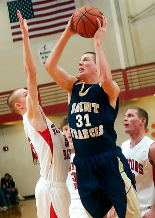 Record-Eagle/Douglas Tesner<br /> Ian Sheldon (31) drives past David Wheelock in St. Francis' 64-52 win over Suttons Bay in the Lake Michigan/Northwest Conference Challenge.