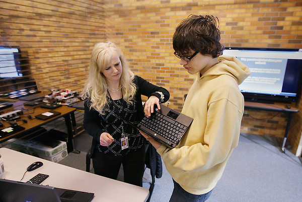 Record-Eagle/Keith King<br /> Tami Navarre, technology assistant, student helps Avery Mackie with a netbook in the tech center at Traverse City Central High School.