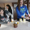 Record-Eagle/Keith King<br /> Amanda Sfeir, left, of Lebanon, and her host sister, Katie Long, of Suttons Bay, use lemons as they make hummus Saturday, February 4, 2012 as Sfeir's host mother, Stephanie Long, in back, walks past.