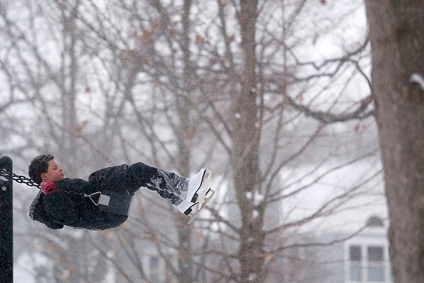 Record-Eagle/Jan-Michael Stump<br /> Devante Walker, 10, takes a break from ice skating at F&M Park to play on the swings on a snowy Monday afternoon.