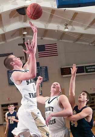 Record-Eagle/Douglas Tesner<br /> TC St. Francis guard Ben Schell puts up a hot over Gaylord's Anthony Rudel (44) and Ian Sheldon (31). Schell scored 14 points in the Gladiator's 53-32 victory.