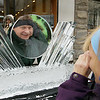 Record-Eagle/Keith King<br /> Steven Sala, of Pinckney, has his photo taken by his wife, Karen Sala, as he stands behind an ice lens sculpture in front of the Camera Shop in downtown Traverse City during the WowFest.