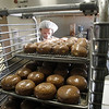 Record-Eagle/Jan-Michael Stump<br /> Mitch Hosler places a tray of freshly glazed paczki on a rack. Potter's added a third machine for faster filling of the approximately 900 dozen paczki they will make this year.