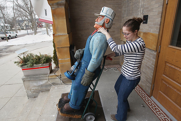 Record-Eagle/Keith King<br /> Maddie Buteyn places a carved wooden statue outside the History Center of Traverse City.