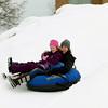 Record-Eagle/Keith King<br /> Jen Ulbrich, of Traverse City, and her daughter, Ella Ulbrich, 6, ride down the tubing hill Saturday during the Cherry Capital Winter WowFest.