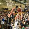 Record-Eagle/Jan-Michael Stump<br /> Traverse City West's Aaron Olsen (14) scores the tying basket over Traverse City Central's Ben Fischer.